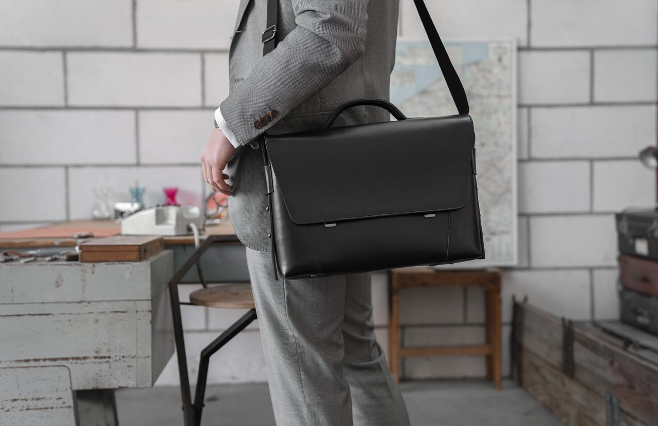 Man carrying the black vegetable-tanned leather briefcase bag with laptop pocket.