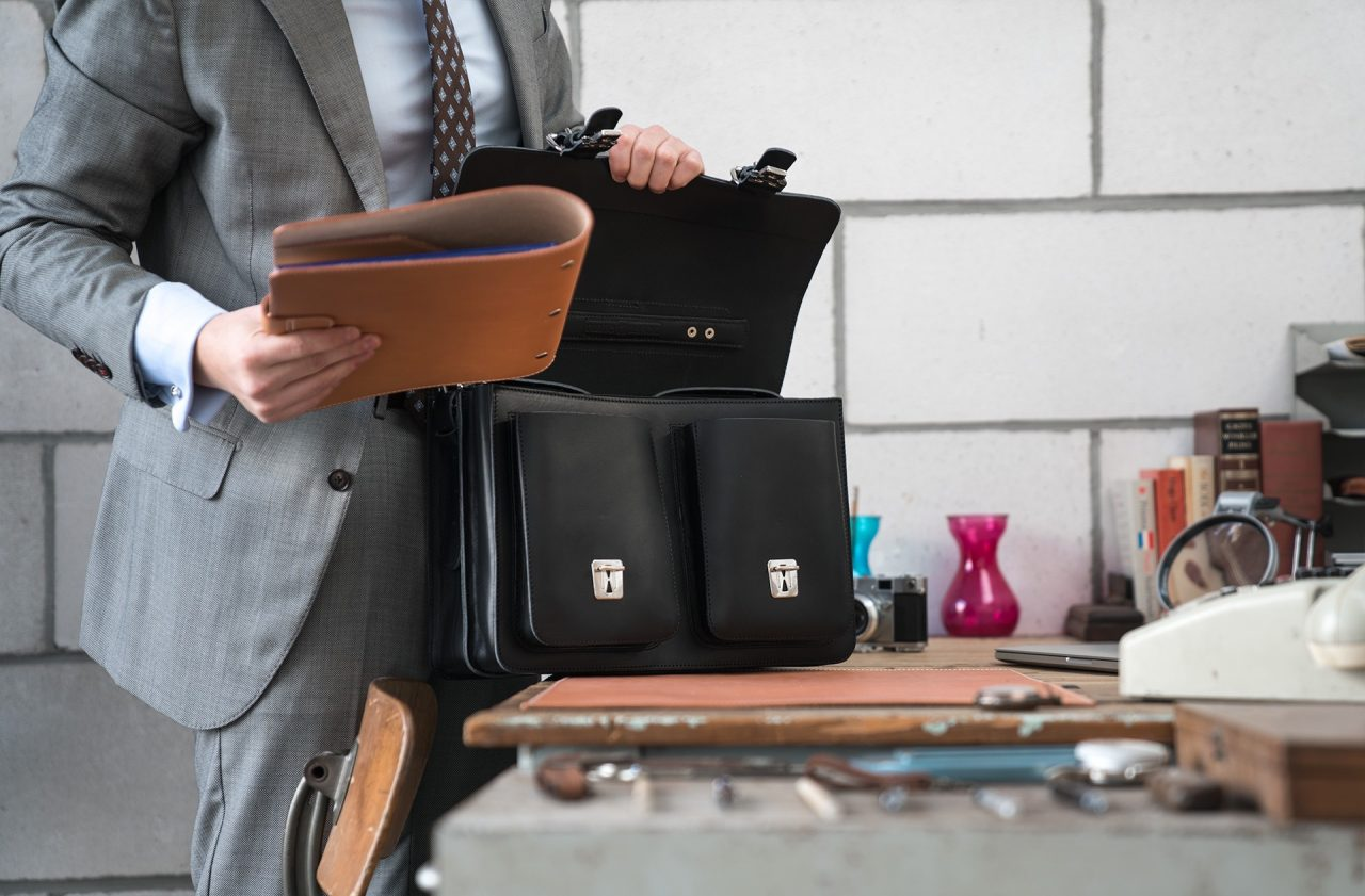 Man using his black leather satchel briefcase with front pockets 112133.