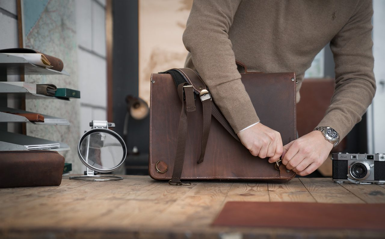 Man fitting his Ruitertassen vintage brown leather satchel with shoulder straps.