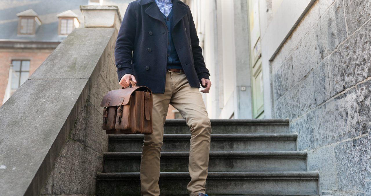 Man carrying his Ruitertassen brown leather satchel by the handle.