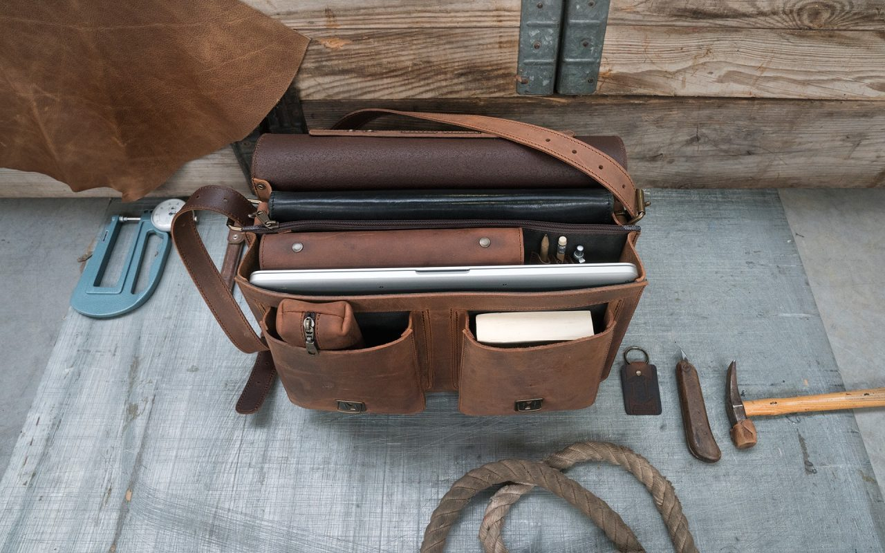 Open brown leather satchel backpack with files and laptop computer.