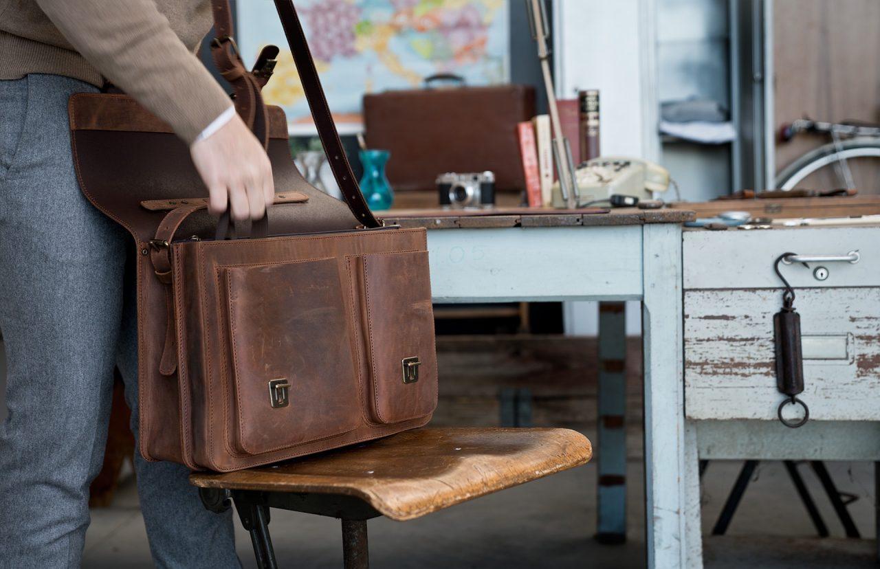 Professor opening his vintage brown Ruitertassen leather satchel briefcase.
