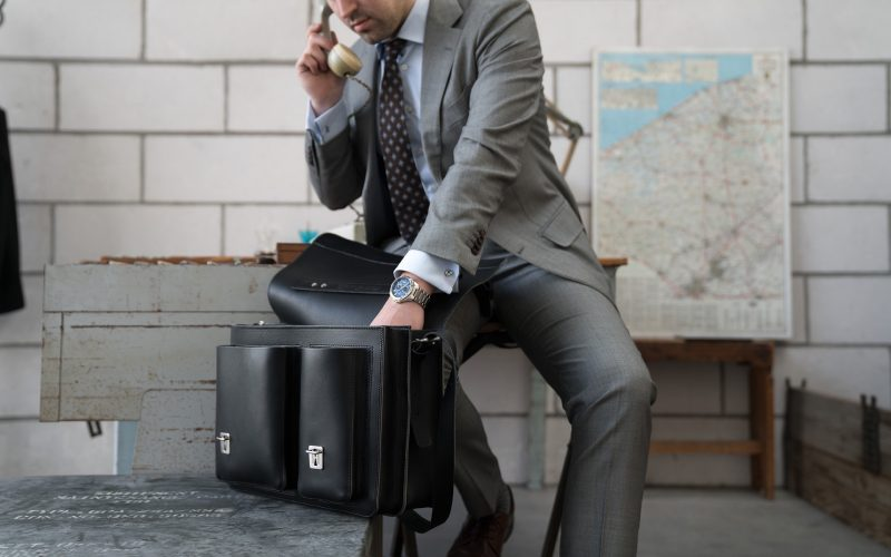 Man using his black leather satchel briefcase with asymmetric front pockets 112137.