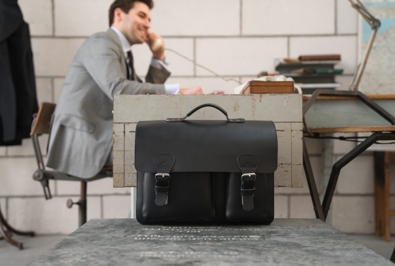 Man in office with large black leather briefcase with 3 compartments and asymmetric front pockets 112142.