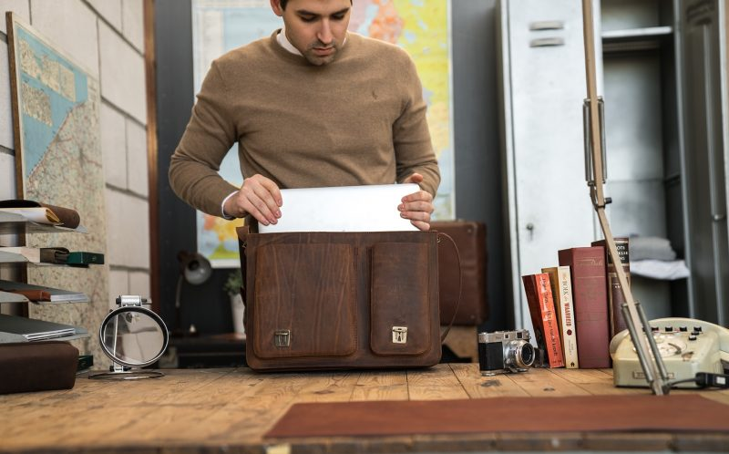 Professor fitting his laptop computer into his Ruitertassen brown leather satchel.