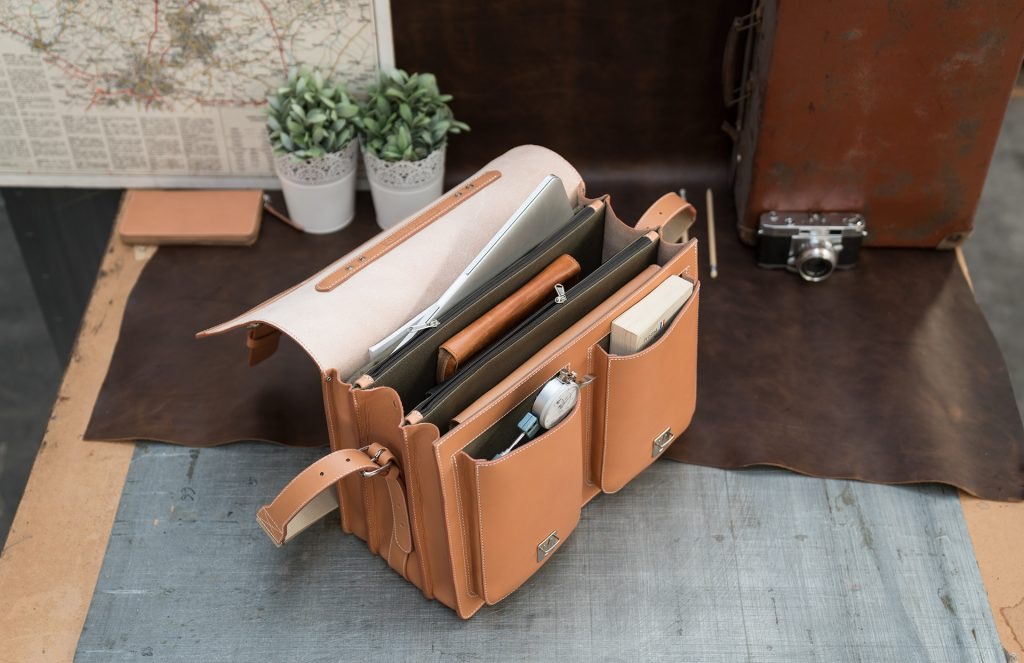 Open large tan leather satchel with laptop computer in pocket.