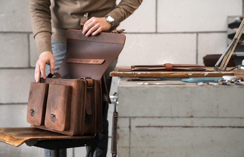 Professor opening his brown Ruitertassen leather satchel briefcase.