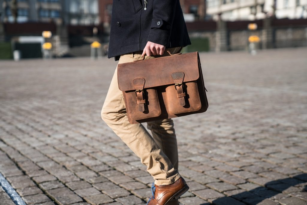 Man holding his brown leather satchel briefcase by the handle in the street.