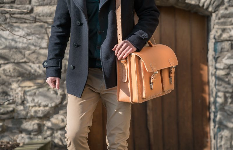 Smart looking man carrying his large tan leather satchel with a shoulder strap.