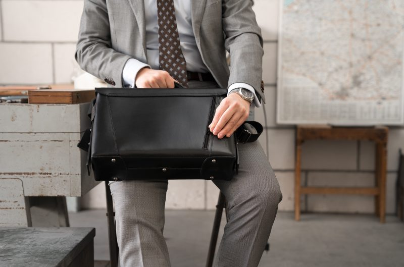 Man opening the back pocket of the black vegetable-tanned leather briefcase bag.