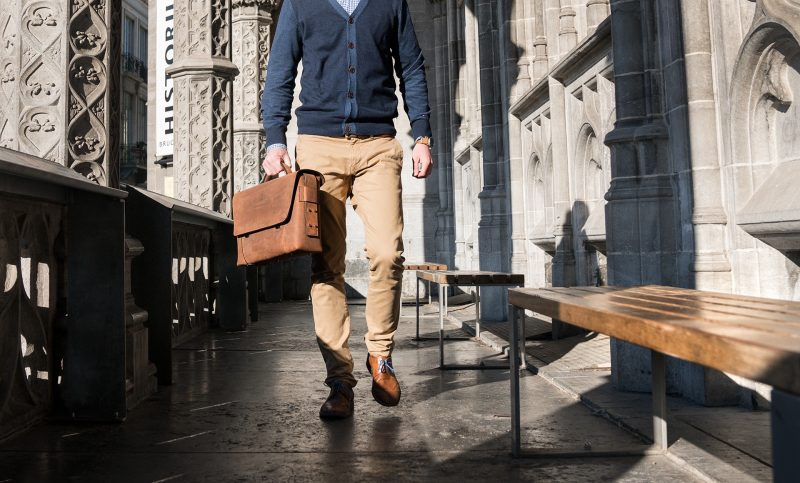 Man carrying the vegetable-tanned brown leather briefcase bag with laptop pocket.
