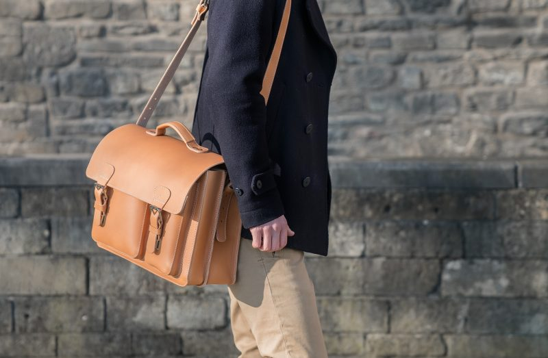 Man carrying his large Ruitertassen tan leather satchel with a shoulder strap.