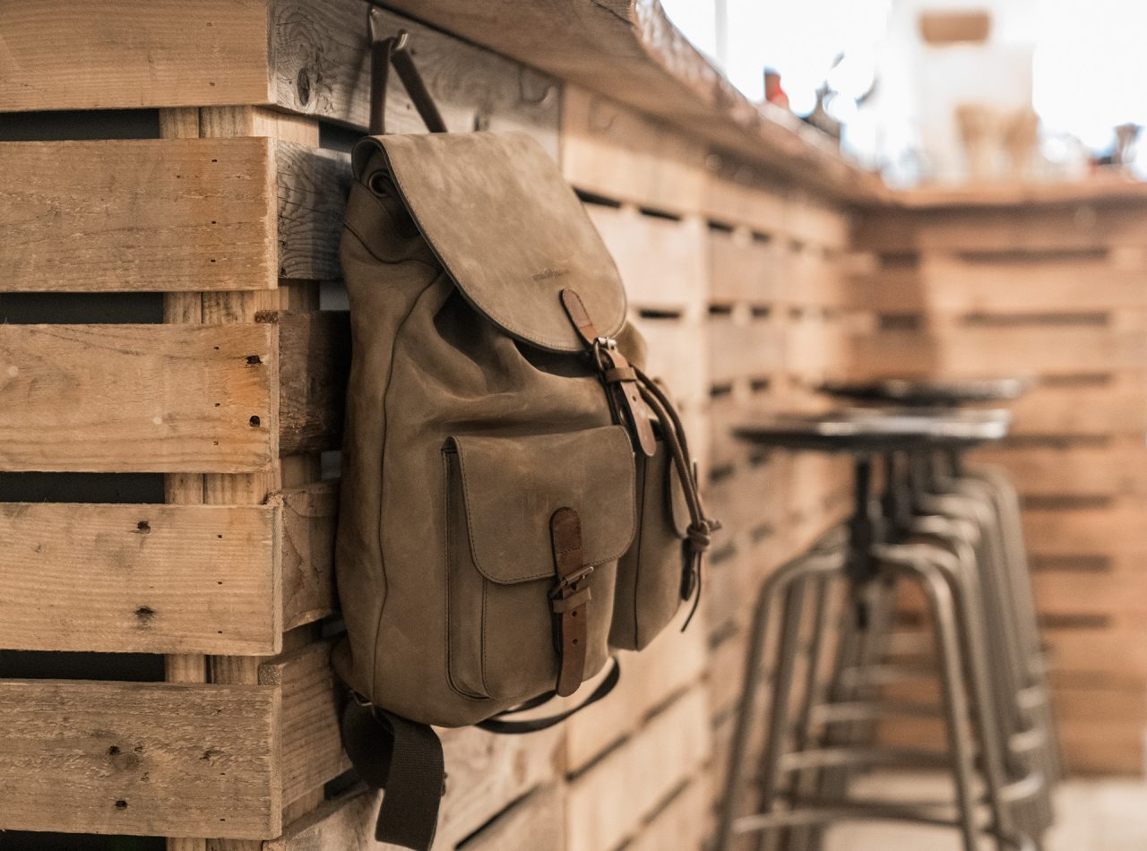 Handmade soft leather backpack hung by its handle.
