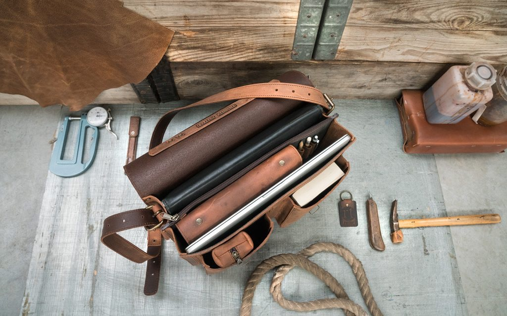 Open brown leather satchel for professors with files, book and macbook laptop.