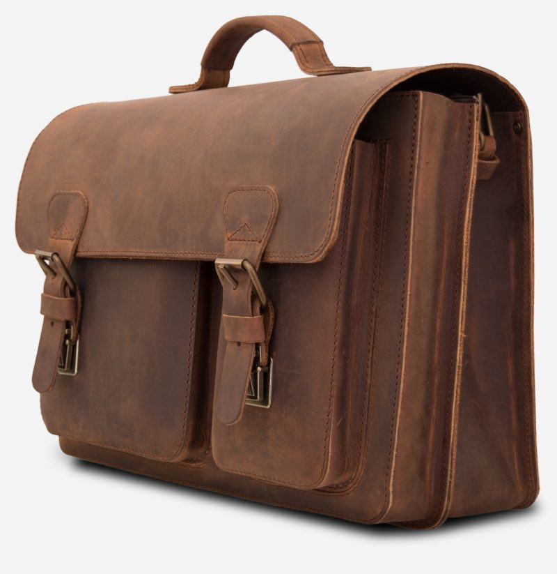 Side view of brown leather satchel with 2 compartments and 2 front asymmetric pockets.