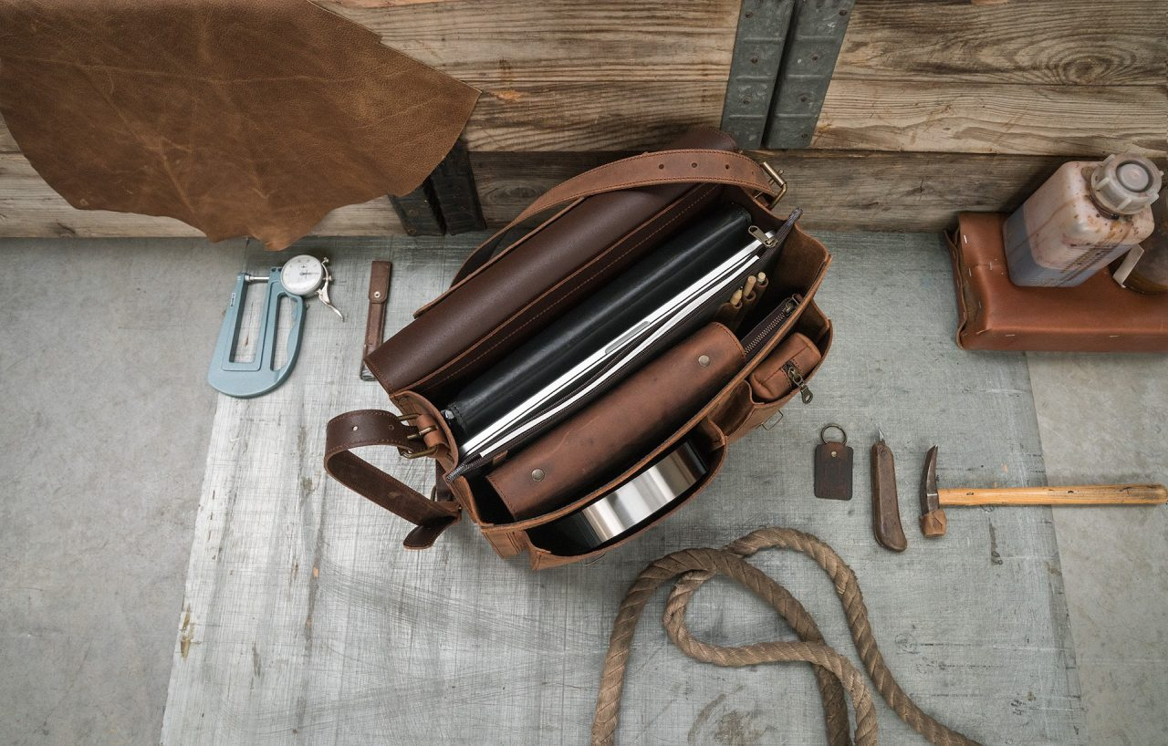 Open brown leather satchel with laptop, files, pencil case and pens.