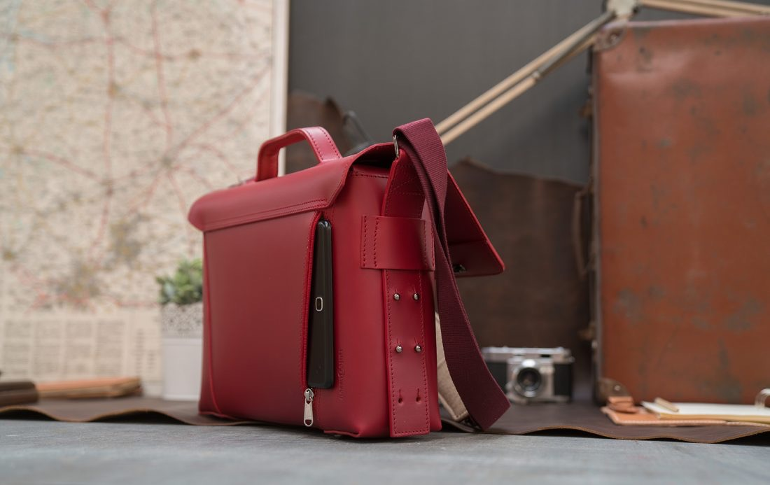 Back view of the elegant red vegetable-tanned leather briefcase bag for women with tablet in back pocket.