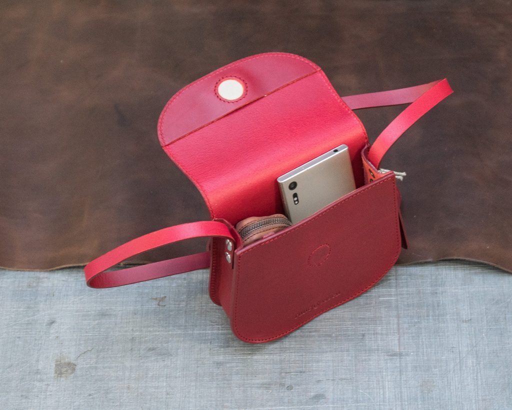 Top view of the small red full-grain leather shoulder bag for women.