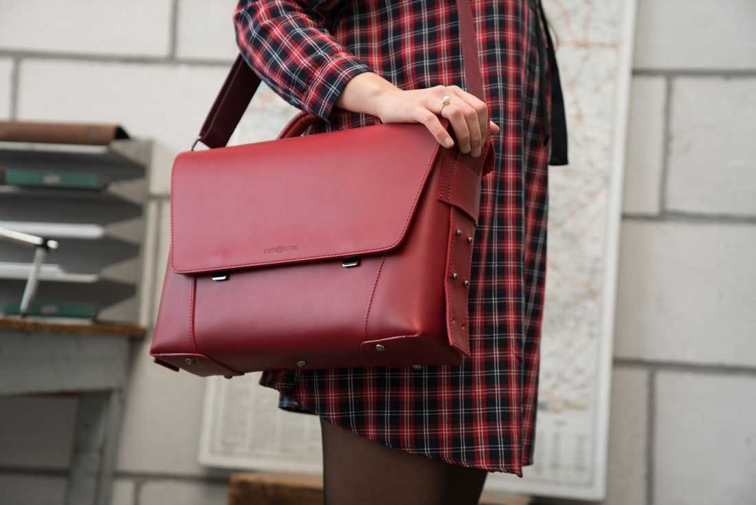 Women wearing the elegant red vegetable-tanned leather briefcase bag on the shoulder.