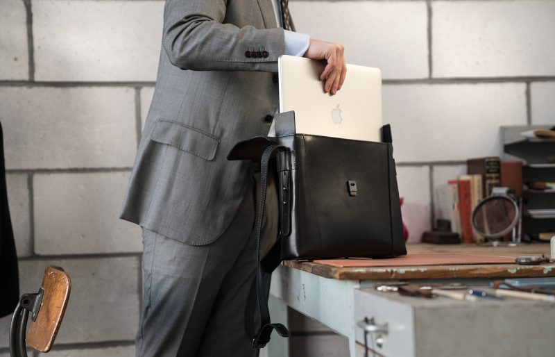 Man fitting his laptop into the slim vegetable-tanned black leather briefcase bag.