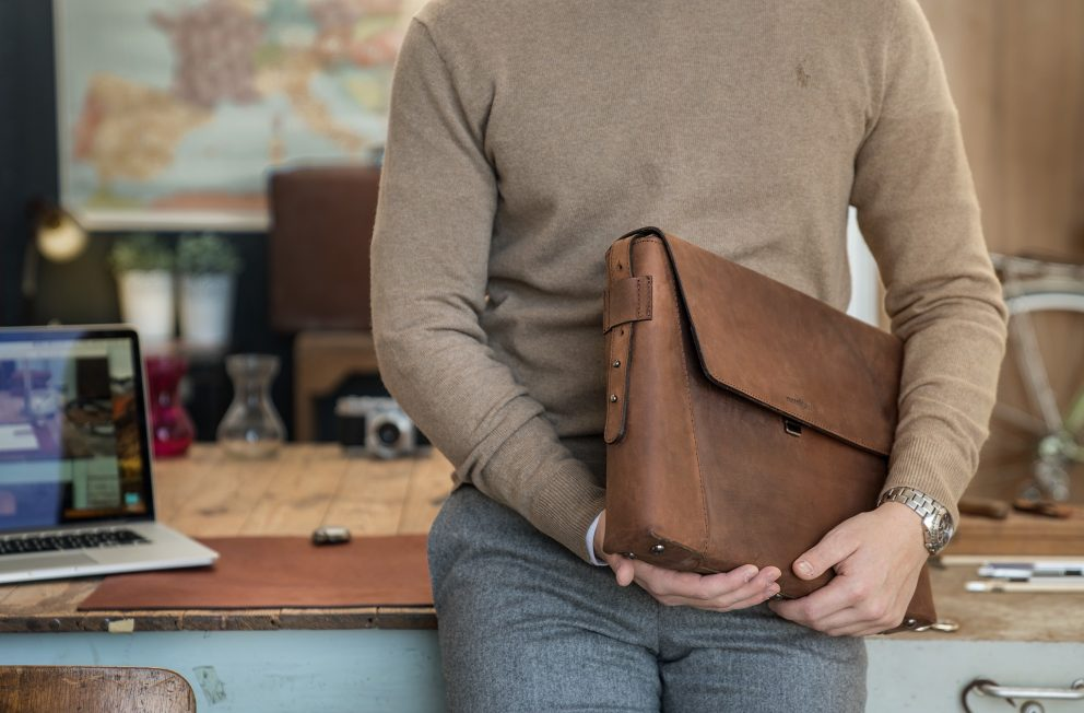 Man holding the slim vegetable-tanned brown leather briefcase bag.