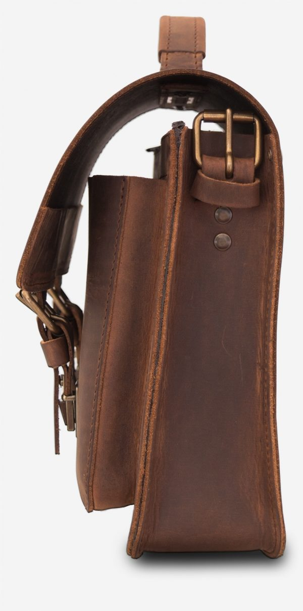 Side view of the brown leather satchel briefcase with one main compartment and two front pockets.