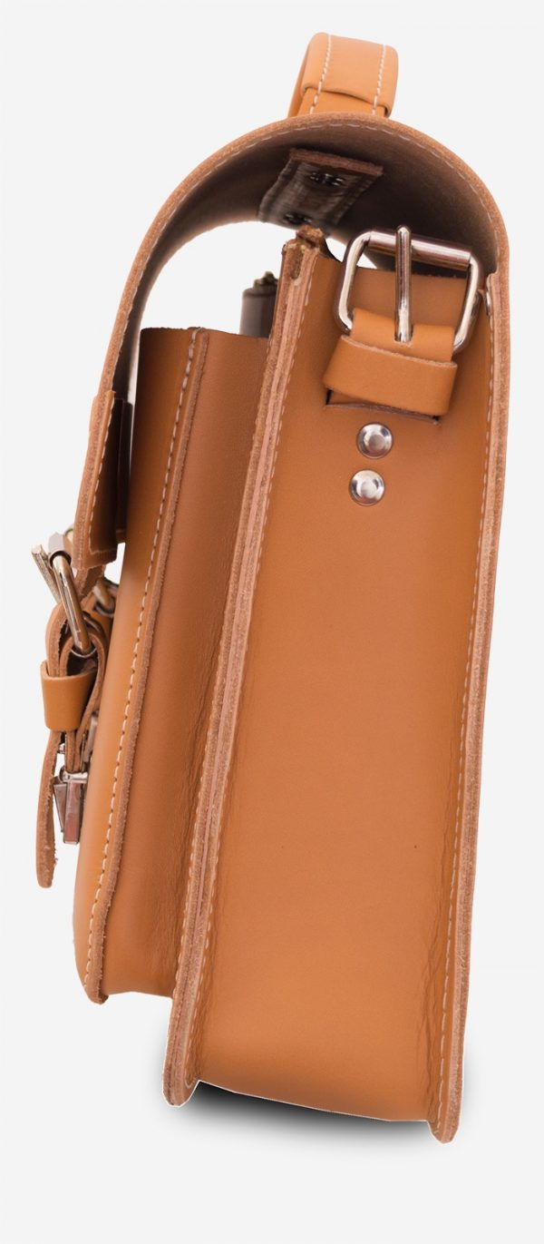 Side view of the tan leather satchel briefcase with one main compartment and two front pockets.