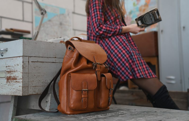 Woman reading next to the elegant brown soft leather backpack.