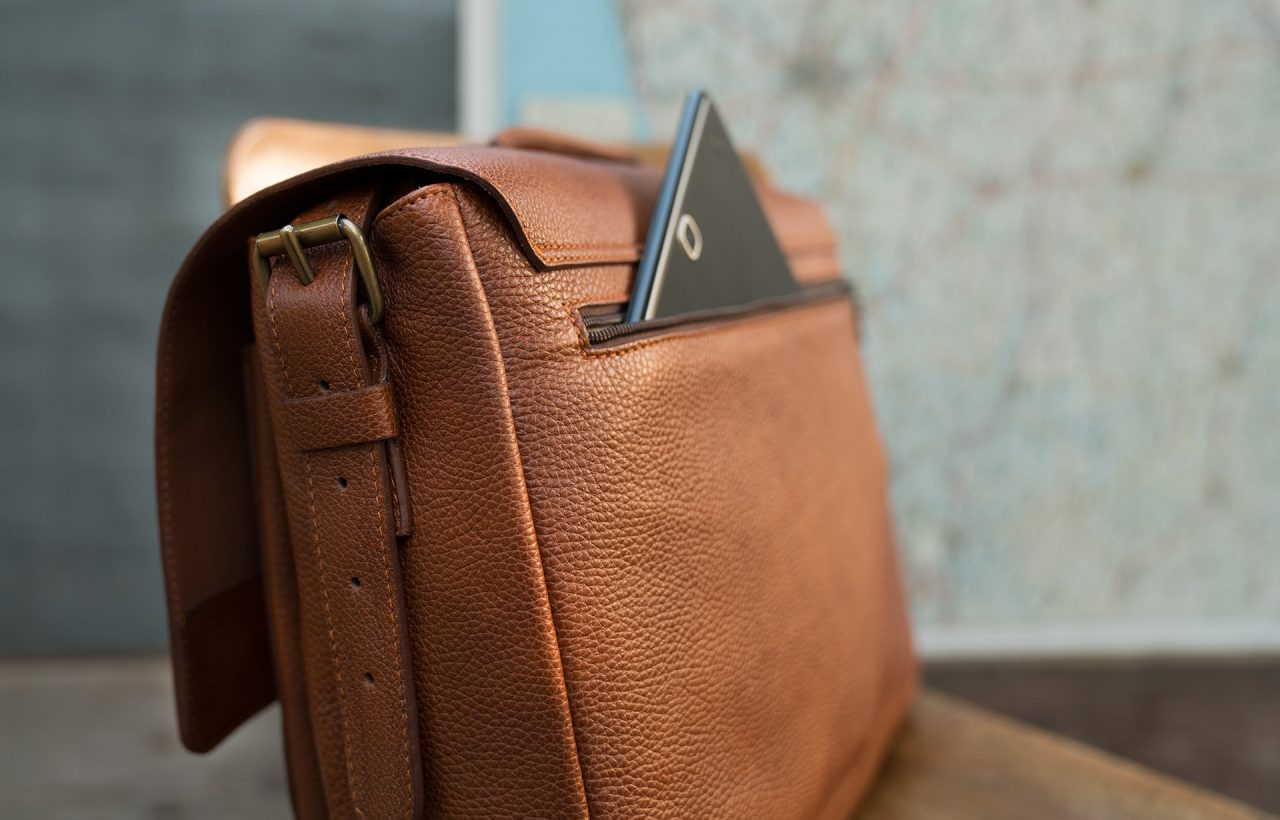 """Back view of the 13"""" soft leather satchel briefcase with tablet in back pocket."""