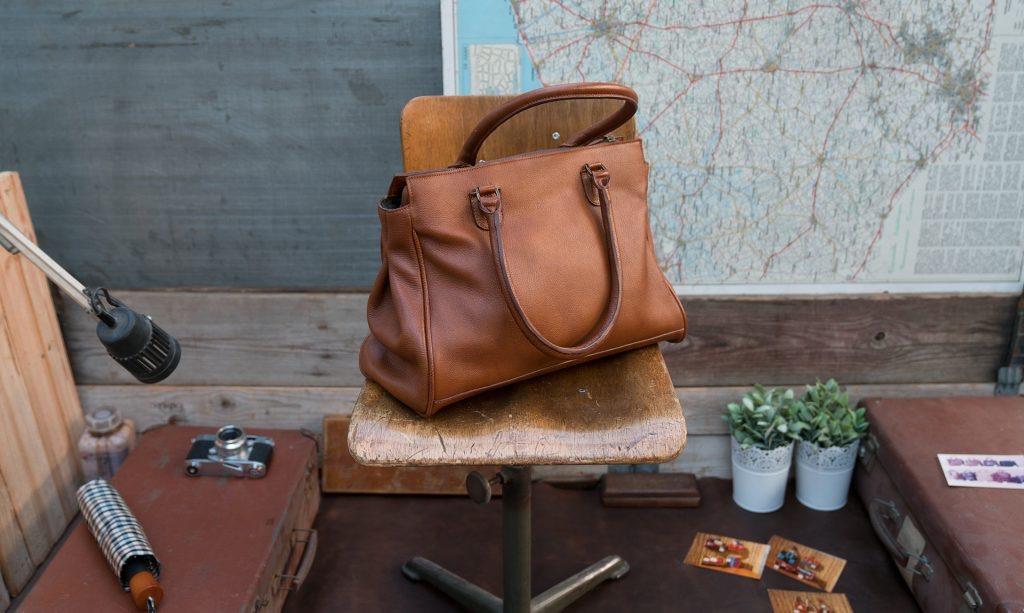 Women soft leather handbag on a chair.
