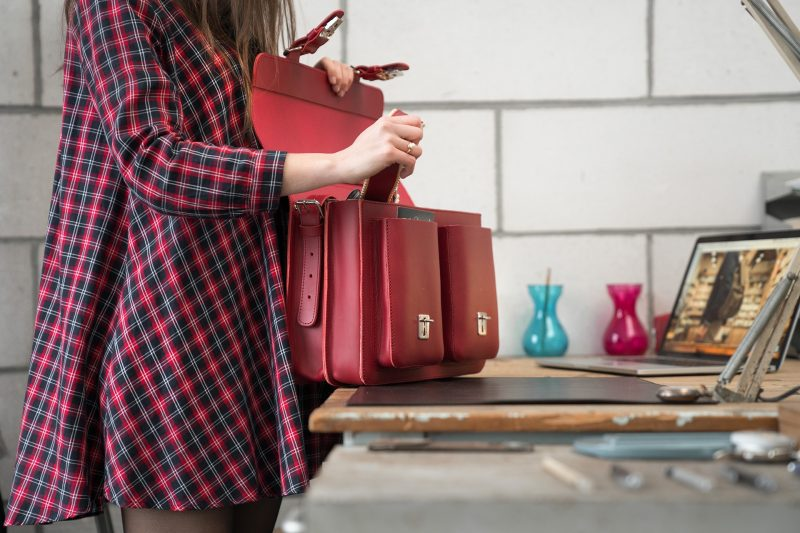 Student opening her red leather satchel backpack with 2 gussets and symmetric front pockets for women - 152233.