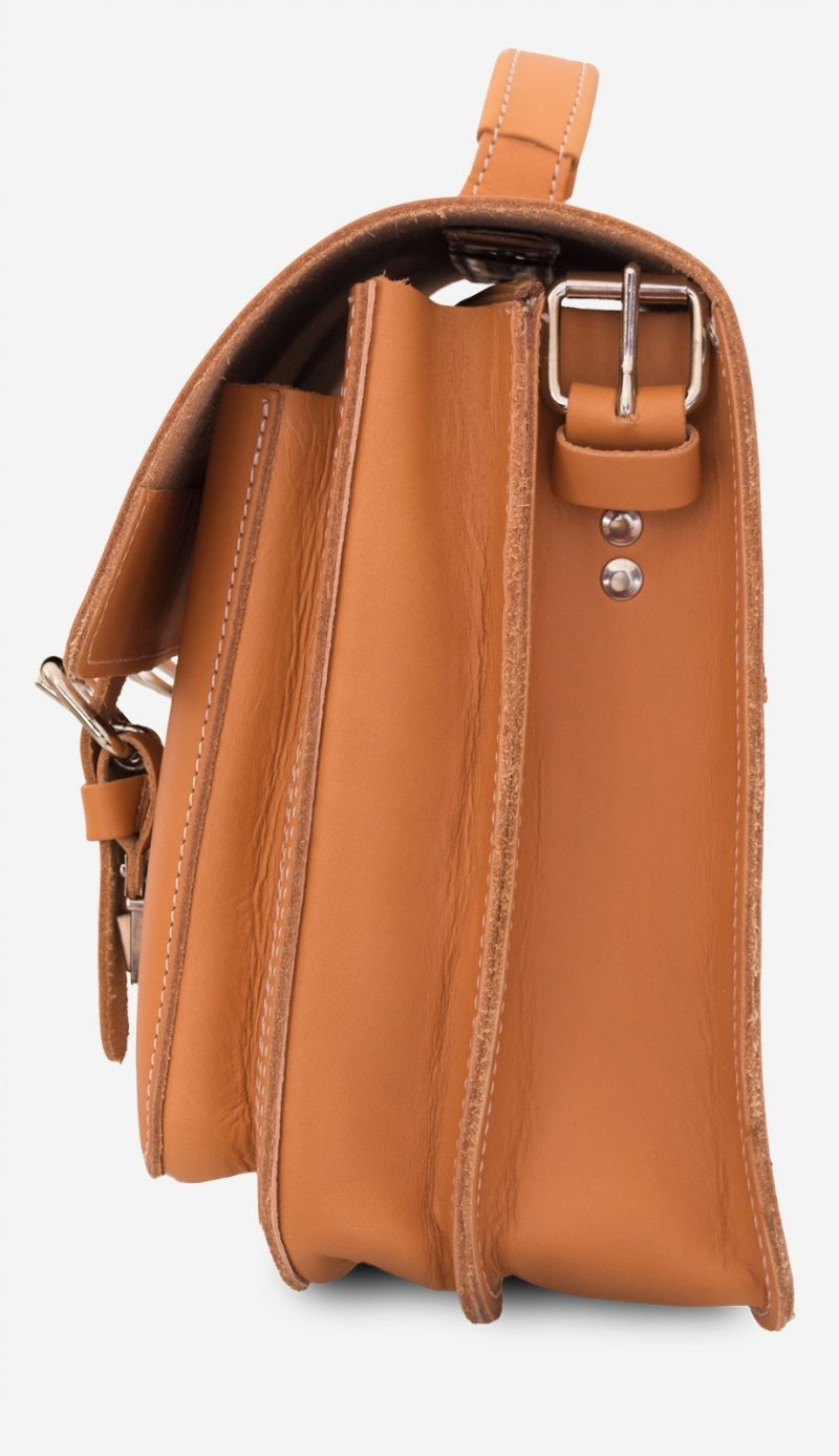 Side view of tan leather satchel bag with 2 compartments and 2 front pockets.