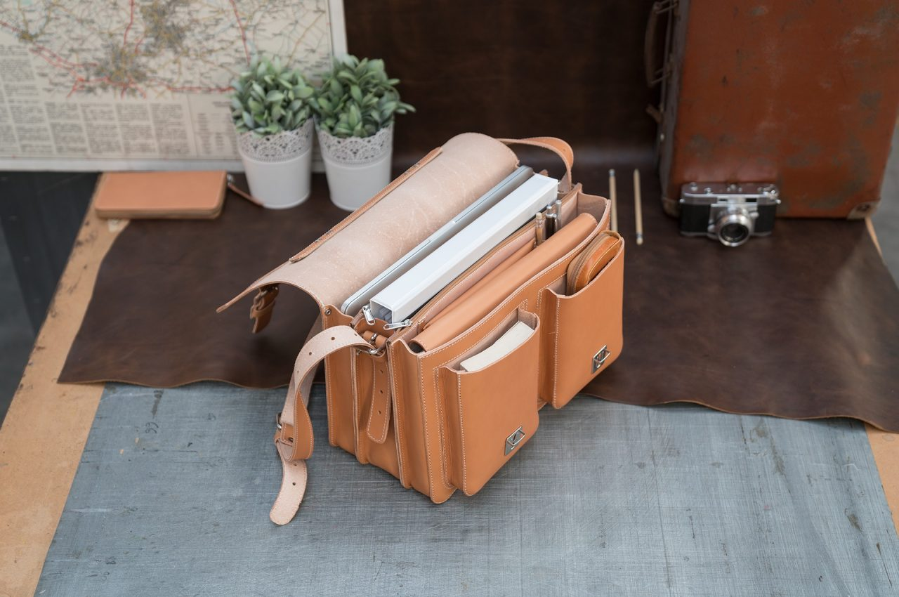 Open Professor tan leather satchel with a large folder, macbook computer, book and pencil case.