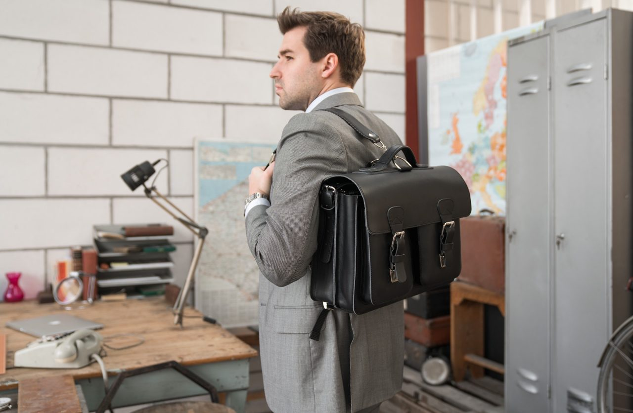 Man carrying his black leather satchel backpack for adults with 2 gussets and symmetric front pockets 112233.