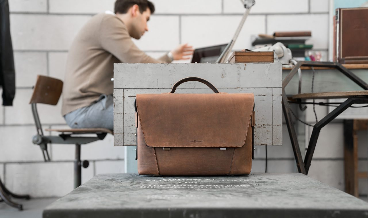 Man in office with the vegetable-tanned brown leather briefcase bag with laptop pocket.