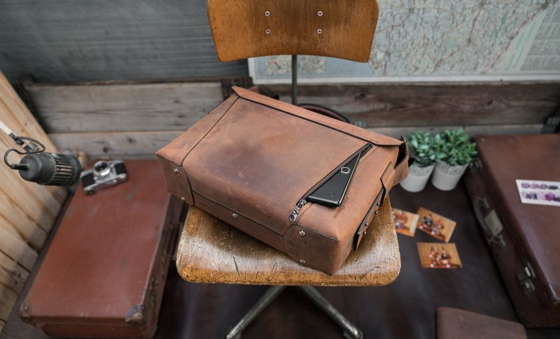 Back view of the vegetable-tanned brown leather briefcase bag with tablet in back pocket.