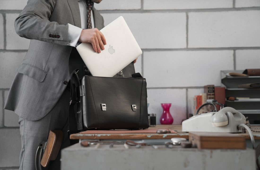 Man fitting his laptop into the black vegetable-tanned leather briefcase bag with laptop pocket.