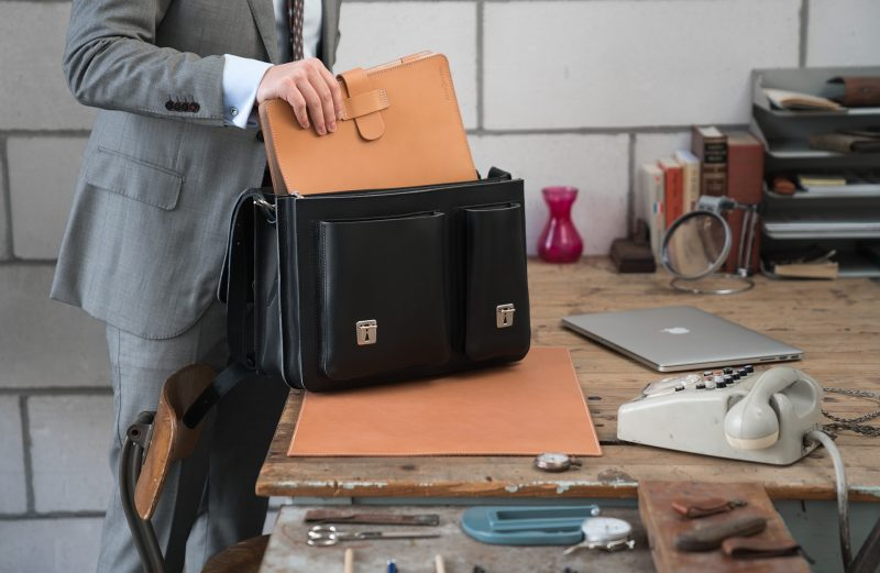 Man using his black leather laptop satchel bag with 2 gussets and asymmetric front pockets 112337.