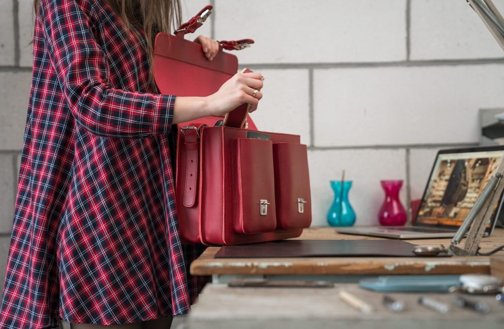 Student opening her red leather satchel briefcase bag with 2 gussets - 152133.