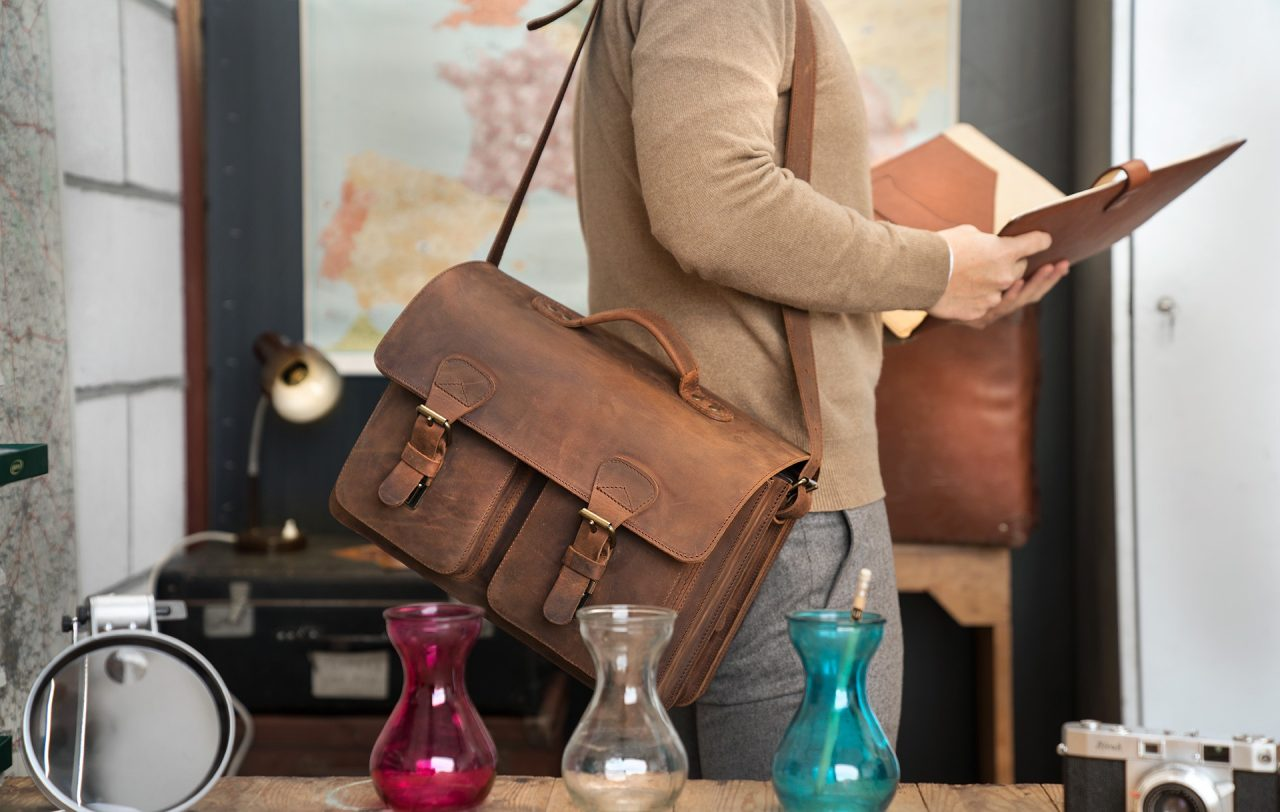 Professor carrying his large vintage brown leather satchel with a shoulder strap.