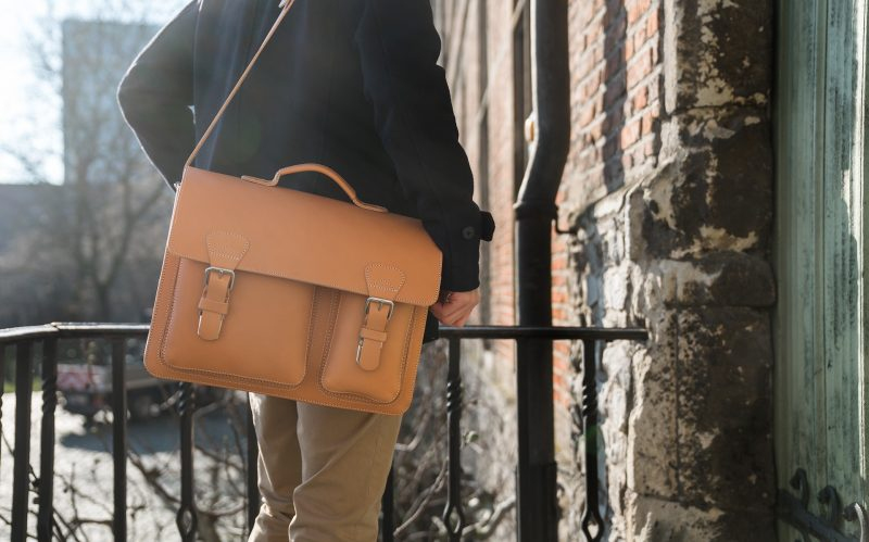 Elegant man carrying is tan leather satchel with a shoulder strap.