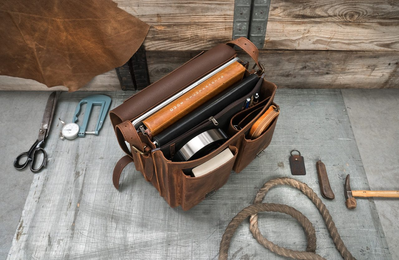 Open brown leather satchel with files, pencil case and pens.