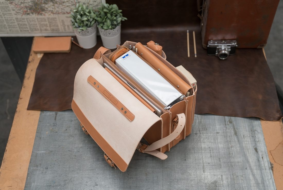 Open large tan leather satchel with large folder and macbook laptop.