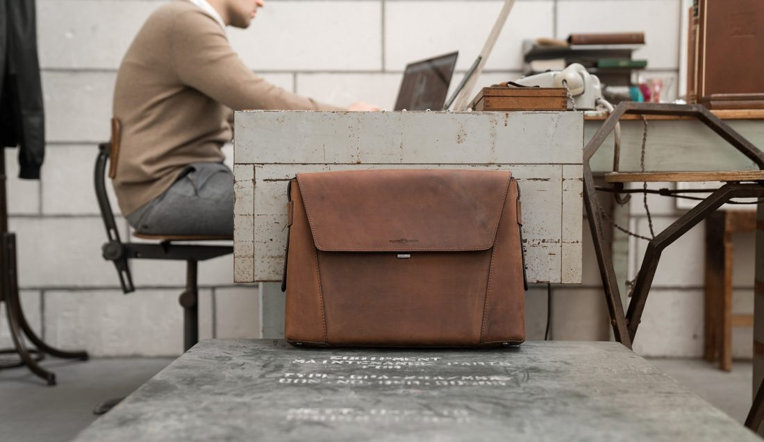Man in office with the slim vegetable-tanned brown leather briefcase bag.