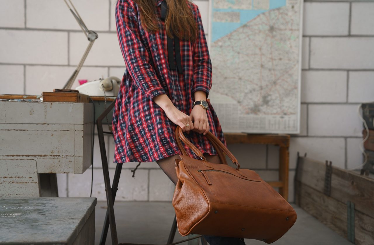 Woman wearing the soft leather handbag for student.