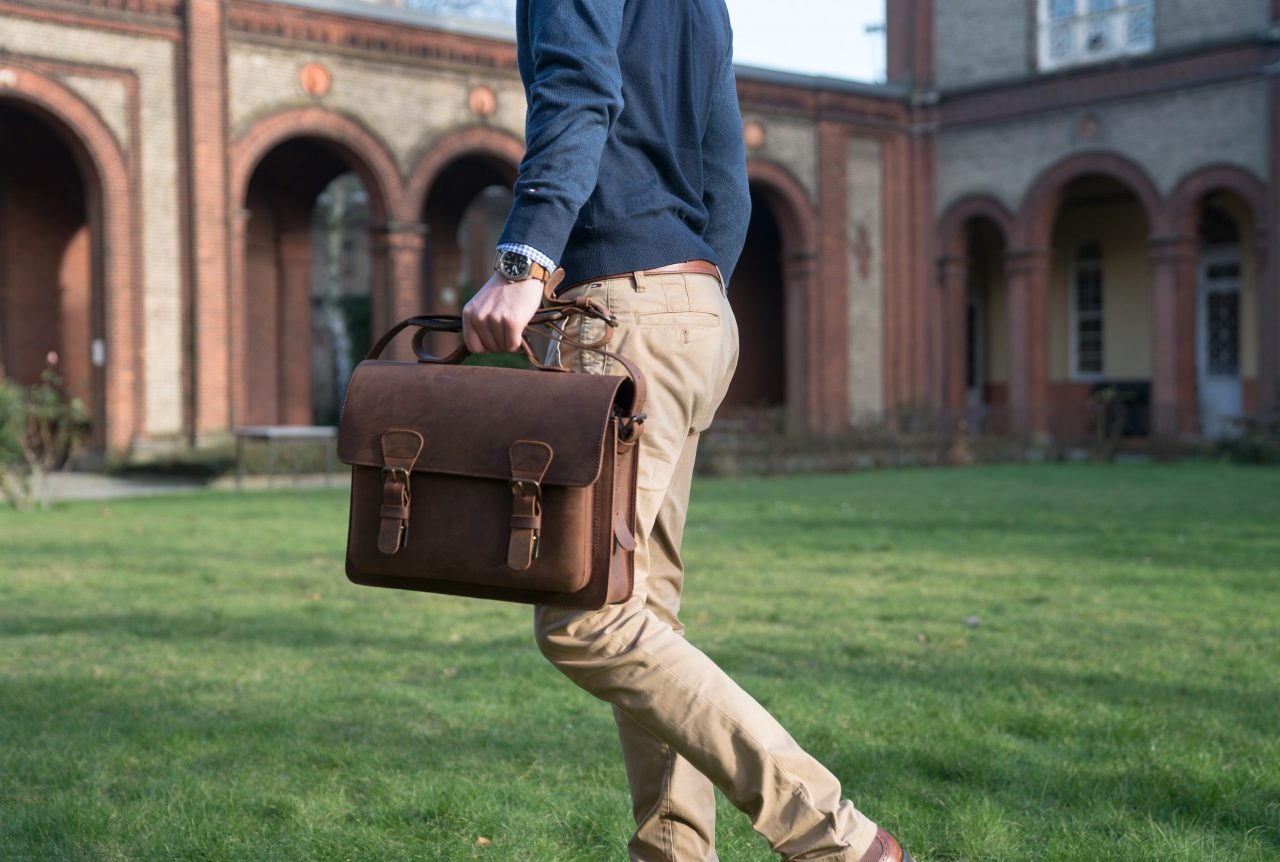 Elegant man holding the brown leather satchel by the handle.