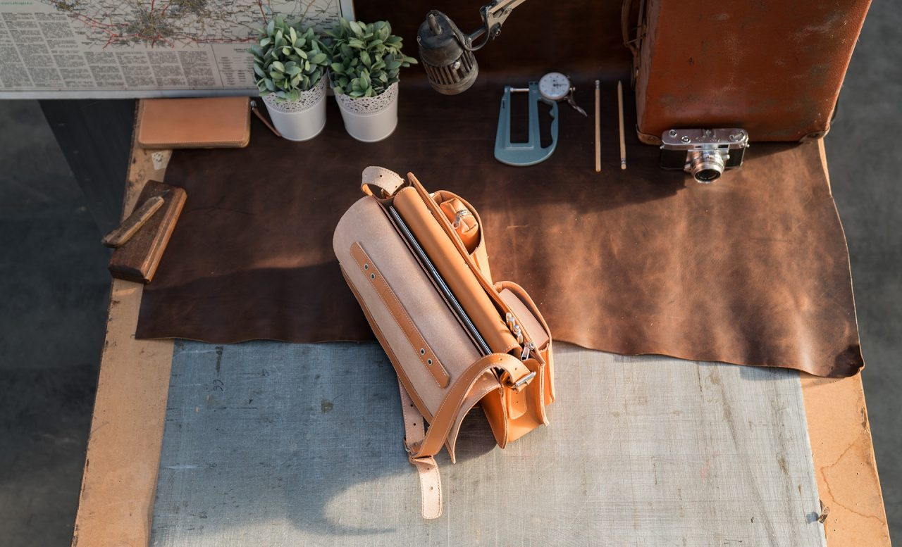 Open tan leather satchel briefcase with a large file, pencil case, book and macbook.