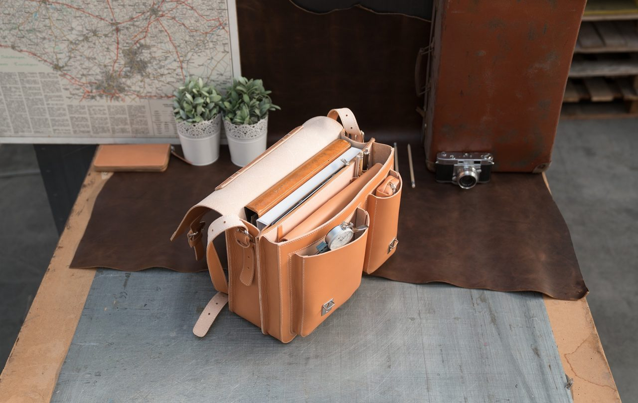 Open tan leather satchel with files, pencil case and pens.