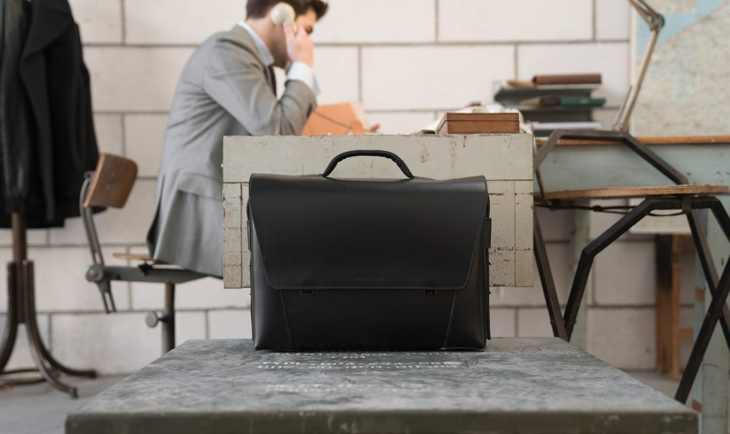 Man in office with the large black vegetable-tanned leather briefcase bag with laptop pocket.