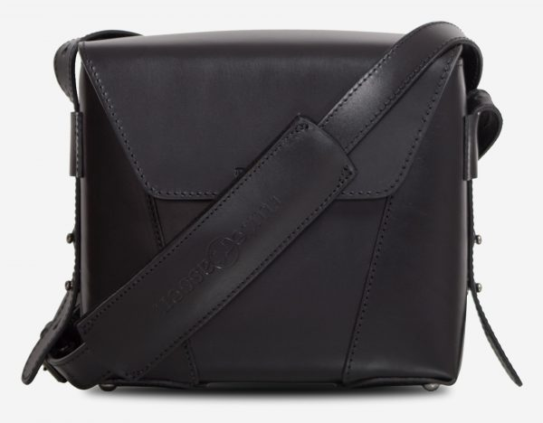 Front view of the small black vegetable-tanned leather crossbody bag with shoulder strap.